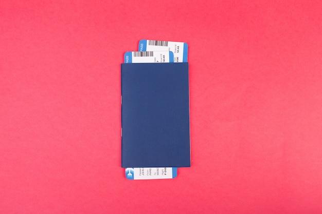 Blauer pass mit zwei flugtickets in ihm auf rosa draufsicht