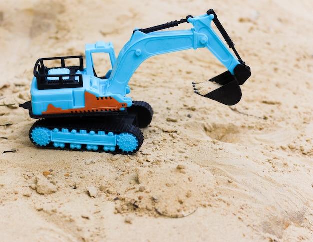 Blauer plastikbagger im sand.