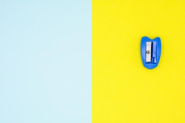 Blauer plastikbleistiftspitzer auf gelbem und blauem hintergrund