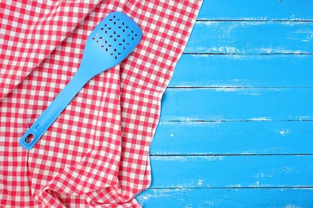 Blauer plastiklöffel mit löchern auf einer roten textilserviette