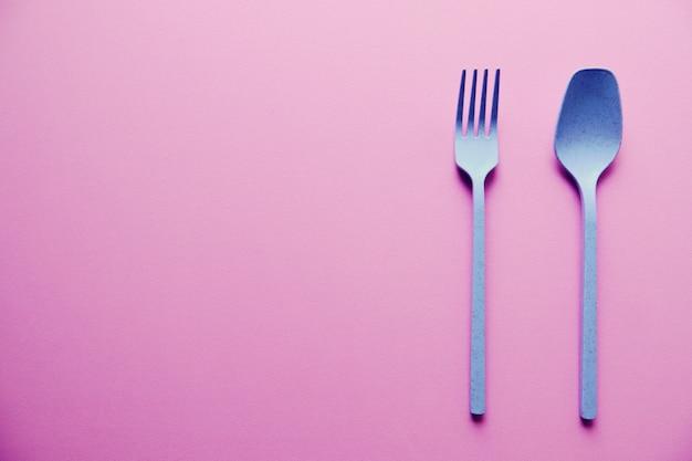 Blauer plastiklöffel und gabel auf rosa hintergrund