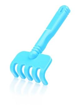 Blauer plastikrechen der kinder auf einem weißen hintergrund. rechen zum spielen im sandkasten, nahaufnahme.