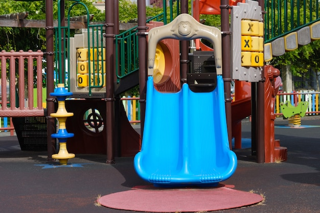 Blauer plastikschlitten auf leerem mehrfarbigem spielplatz