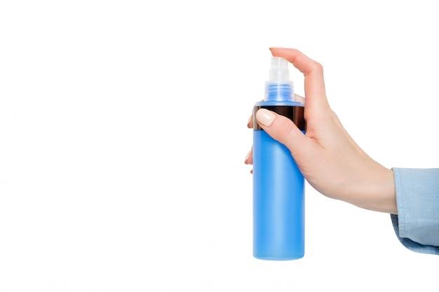 Blauer plastikspray für kosmetik in einer weiblichen hand. isolieren