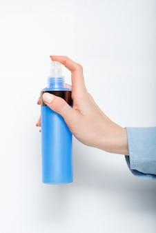 Blauer plastikspray für kosmetik in einer weiblichen hand
