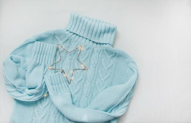 Blauer pullover, gestrickte fäustlinge und weihnachtsschmuck