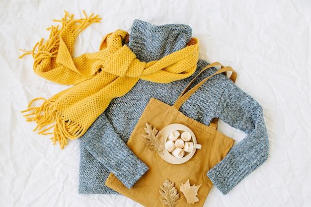 Blauer pullover mit gelbem strickschal und tragetasche mit kakaogetränk. herbst-/wintermode-kleidungscollage auf weißem hintergrund. draufsicht flach.
