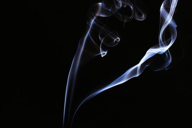 Blauer rauch bewegt auf schwarzen hintergrund wellenartig
