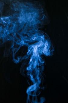 Blauer rauch, der auf schwarzem hintergrund wirbelt