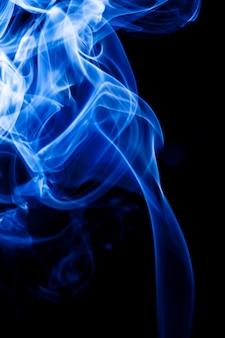 Blauer rauch der bewegung auf schwarzem hintergrund.