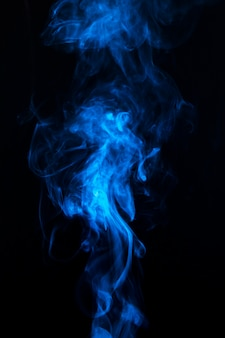 Blauer rauch, der herum gegen einen schwarzen hintergrund wirbelt