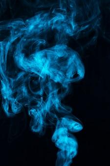 Blauer rauch des dampfes verbreitete gegen schwarzen hintergrund