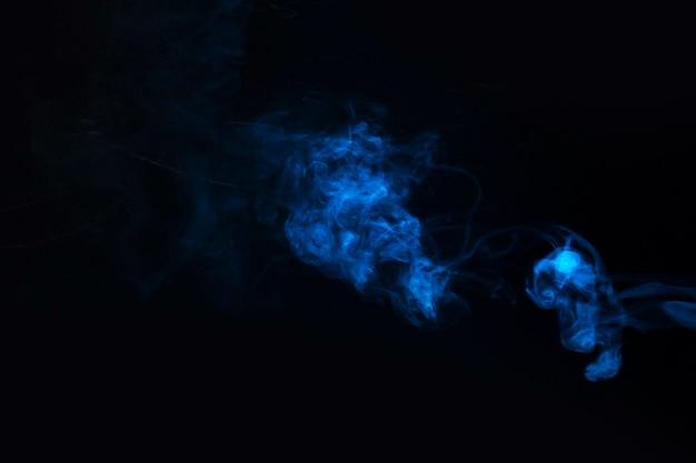 Blauer rauch gegen schwarzen hintergrund