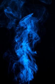 Blauer rauch in der mitte des schwarzen hintergrundes