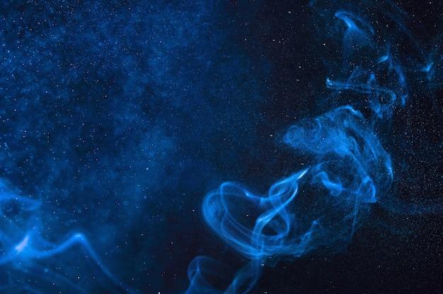Blauer rauch und sprühnebel des wassers auf einem schwarzen hintergrund