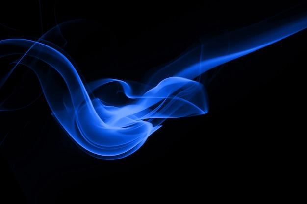 Blauer rauchauszug auf schwarzem hintergrund. dunkelheitskonzept