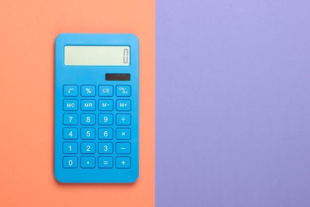 Blauer rechner auf lila orange pastellhintergrund. berechnung oder zählung. minimalismus. speicherplatz kopieren. draufsicht