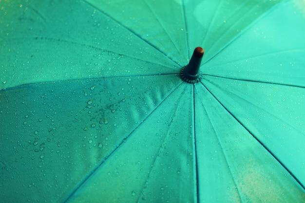 Blauer regenschirm mit regentropfen. herbstwetter-konzept