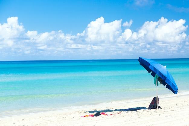 Blauer regenschirm mit tasche und handtuch am ozeanstrand mit schönem blauen himmel und wolken