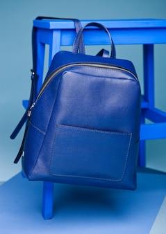 Blauer rucksack, der von einer tabelle hängt