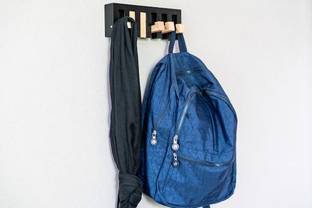 Blauer rucksack hängt am hölzernen aufhänger auf weißer wand.