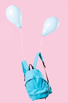 Blauer rucksack mit luftballons zusammengebunden