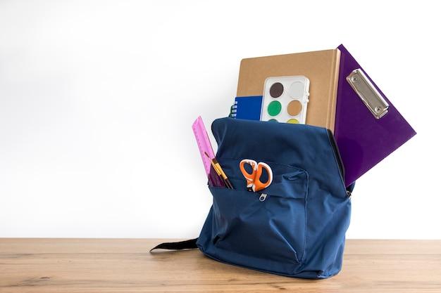 Blauer rucksack mit schulmaterial