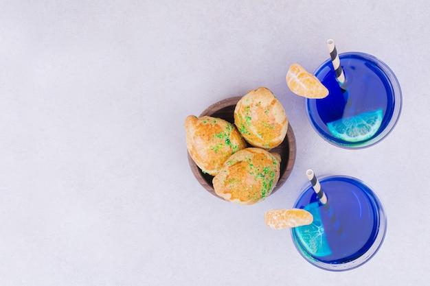 Blauer saft in gläsern mit mandarinenscheiben.