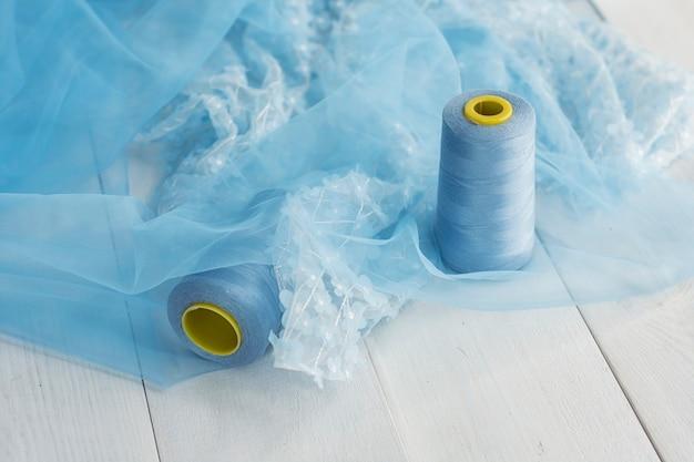 Blauer satinstoff mit fäden auf holzuntergrund mit perlen.