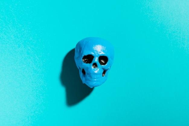 Blauer schädel der draufsicht auf blauem hintergrund