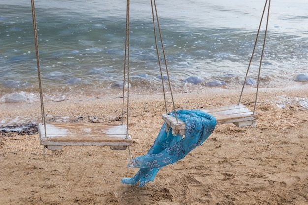 Blauer schal auf einer schaukel am meer. algen auf sand. quallen im wasser.