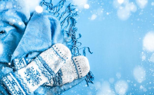 Blauer schal und handschuhe auf blauem hintergrund, kopienraum