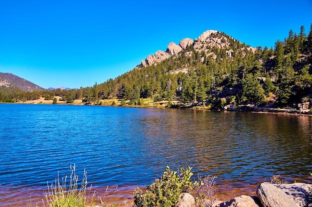 Blauer see mit felsigem berg im hintergrund und strahlend blauem himmel