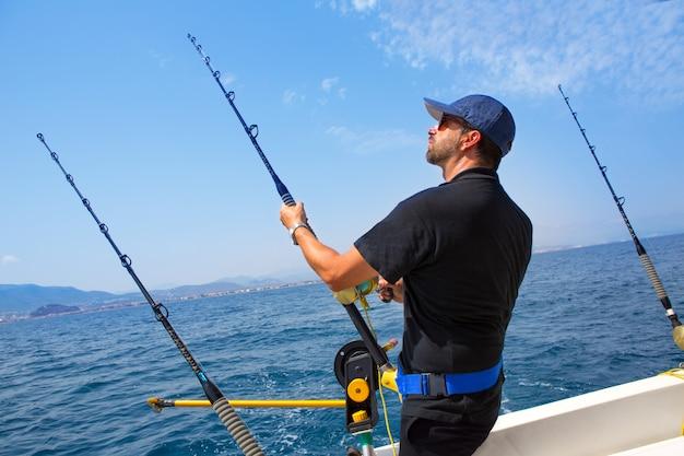 Blauer seefischer im trollenden boot mit downrigger