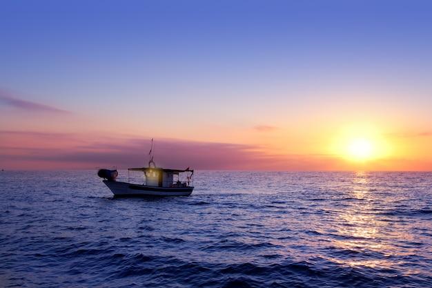 Blauer seesonnenaufgang mit sonne im horizont