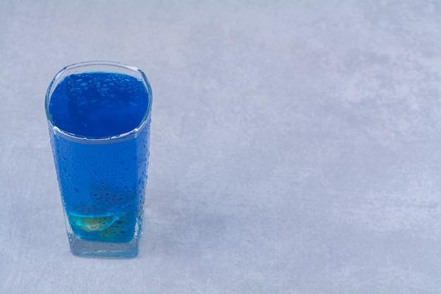 Blauer smoothie in einem glas auf dem marmortisch.
