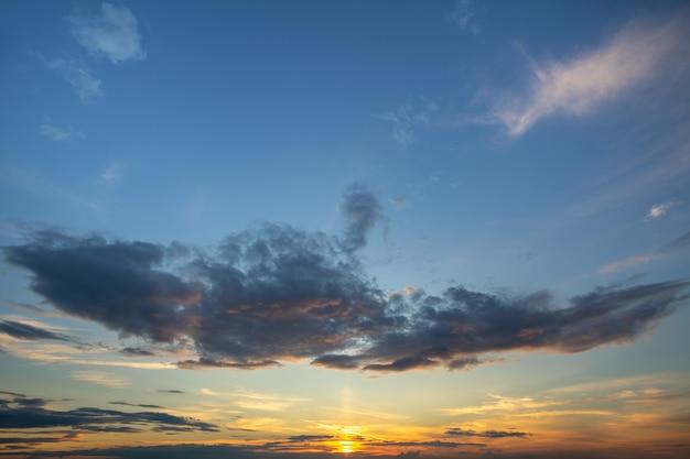 Blauer sonnenunterganghimmel bedeckt mit weißen geschwollenen wolken.