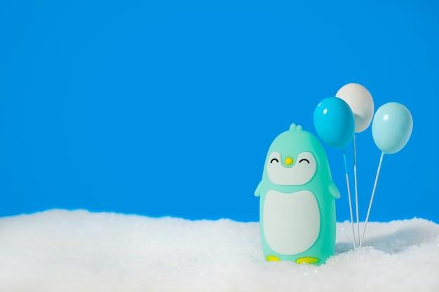 Blauer spielzeugpinguin mit luftballons auf blau.