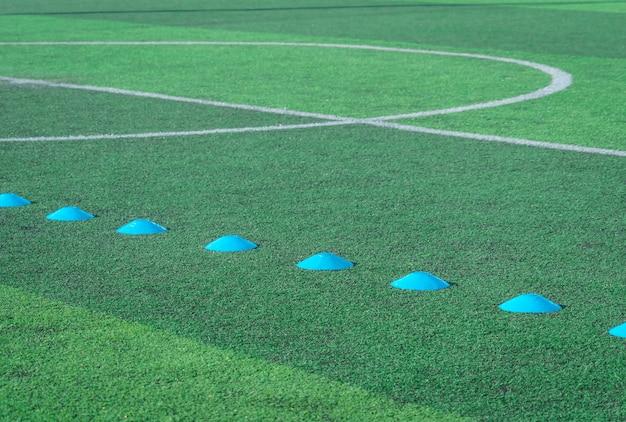 Blauer sportmarker auf grünem kunstrasenfußballfußballplatz