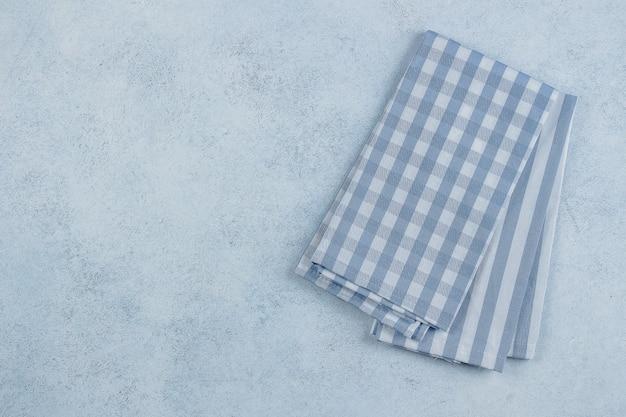 Blauer steintisch mit blau karierter und gestreifter servietten tischdecke.