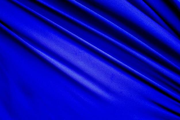 Blauer stoffbaumwollhintergrund. display abstrakte textur luxus tuch weiche welle. für gute verwendung von text präsentieren oder fördern sie ihre waren, produkte auf freiraumhintergrund. ansicht von oben oder flach.
