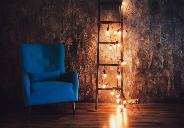 Blauer stuhl in einem dunklen raum und leiter mit lichtern