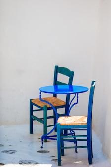 Blauer stuhl und tabelle auf straße des typischen griechischen traditionellen dorfs auf mykonos-insel, griechenland, europa