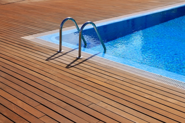 Blauer swimmingpool mit teakholzboden