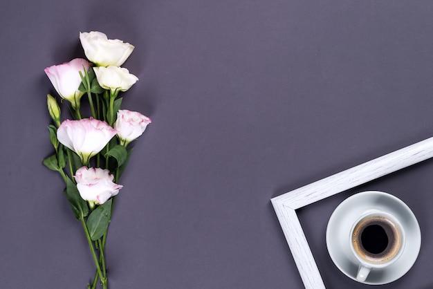 Blauer tasse kaffee mit blühendem rosa eustoma des blumenstraußes auf einem schwarzen papierhintergrund mit copyspace, flache lage.