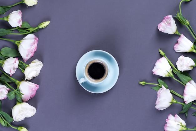Blauer tasse kaffee mit blühendem rosa eustoma des blumenstraußes, flache lage.