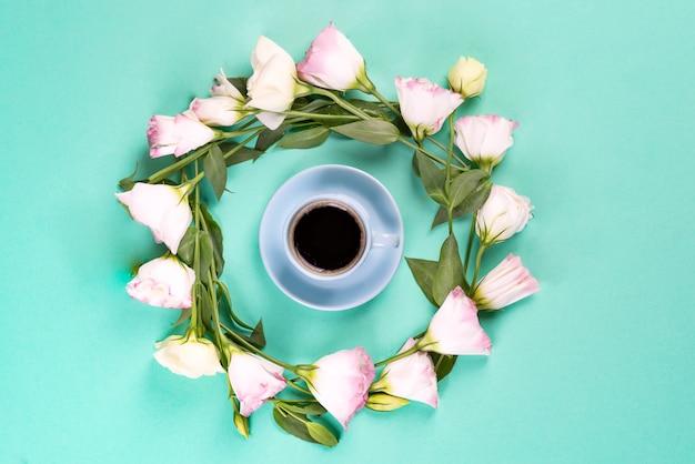 Blauer tasse kaffee mit dem kranz gemacht von rosa blumen eustoma