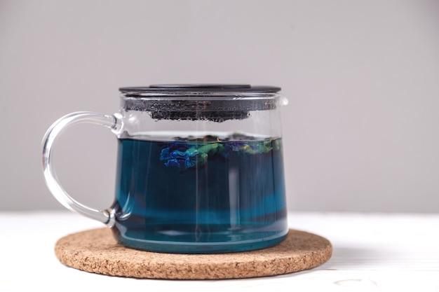 Blauer tee der schmetterlingserbsenblume. gesundes detox-kräutergetränk. schmetterlingserbsentee in der transparenten teekanne auf weißem holztisch