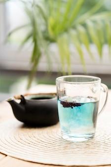 Blauer tee im glas nahe teekanne