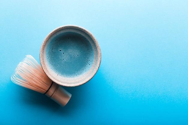 Blauer tee matcha in schüsseln und chasen auf betondecke